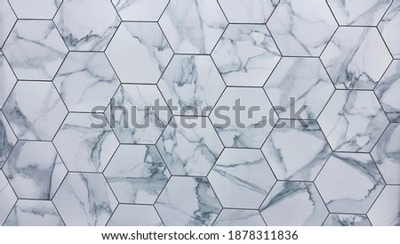 Hexagon marble or granite tiles newly installed on the kitchen backsplash, modern design of gray and white porcelain flooring tiles and it can be install on shower walls or floors. Showroom detail.