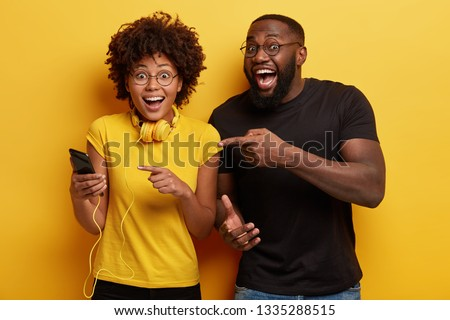Hey, have look at screen of cellular. Horizontal shot of overjoyed African American woman has headphones and cell phone, surprised to have update playlist, curious man points at modern device
