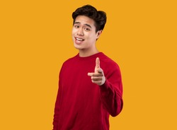 Hey, It's You. Portrait of young asian man in red sweater pointing index finger at camera, posing isolated over orange background wall. Cheerful smiling guy picking, choosing and indicating