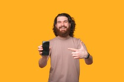 Hey look at this offer, happy bearded man pointing at smartphone.