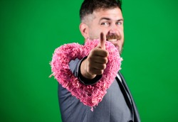 Hey pretty. Spread love around. Happy in love. Romantic macho flirting. Happy valentines day. Hipster hold heart symbol love. Man formal suit celebrate valentines day green background