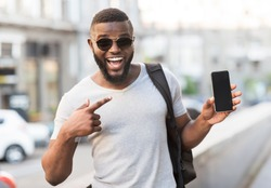 Hey something new. Happy african guy pointing his cellphone with black blank screen for advertisement outdoor, panorama