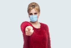 Hey you. are you stay at home? Portrait of serious woman with surgical medical mask in red blouse standing, pointing and looking at camera and blame. indoor studio shot isolated on gray background.