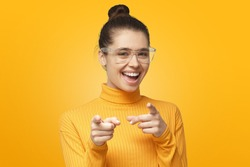 Hey you! Beautiful young female pointing to camera with fingers isolated on yellow background