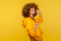 Hey you, handsome! Portrait of joyful curly-haired woman in urban style hoodie winking playfully and pointing to camera, choosing guy and flirting. indoor studio shot isolated on yellow background