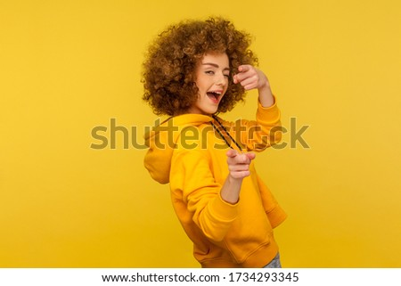 Hey you, handsome! Portrait of joyful curly-haired woman in urban style hoodie winking playfully and pointing to camera, choosing guy and flirting. indoor studio shot isolated on yellow background Foto stock ©