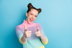 Hey you. Photo of attractive crazy funky lady two buns directing fingers on camera blinking eye flirty person pick select wear casual warm striped sweater isolated blue color background