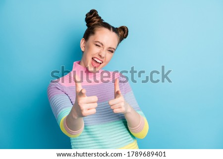 Hey you. Photo of attractive crazy funky lady two buns directing fingers on camera blinking eye flirty person pick select wear casual warm striped sweater isolated blue color background Foto stock ©