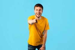 Hey, You. Portrait of cheerful casual man pointing finger at camera, standing isolated over blue studio background wall, copy space. Guy choosing and indicating. Gotcha