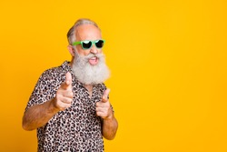 Hey you! Portrait of funky old bearded man in eyeglasses eyewear  feel cool crazy point at you  wearing leopard shirt isolated over yellow background