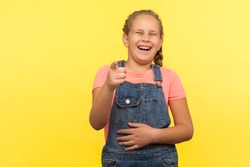 Hey you! Portrait of glad little girl with braid in denim overalls pointing finger to camera and laughing loudly, holding belly with crazy laughter, teasing making fun of you. studio shot, isolated