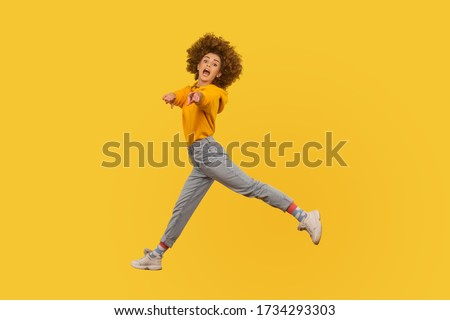 Hey you! Portrait of lively energetic curly-haired girl in urban style outfit walking through air in wide strides, pointing to camera and shouting message. studio shot isolated on yellow background Foto stock ©