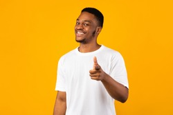 Hey, You. Positive African Guy Pointing Fingers At Camera Posing On Yellow Background. Studio Shot
