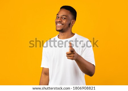 Hey, You. Positive African Guy Pointing Fingers At Camera Posing On Yellow Background. Studio Shot Foto stock ©