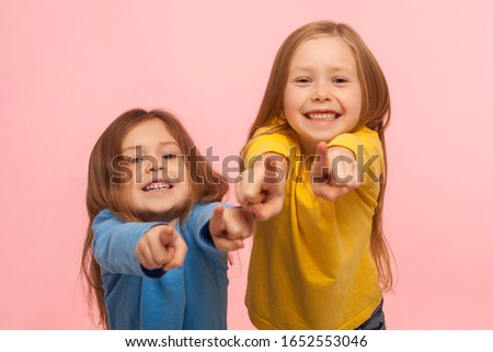 Hey you! Two charming happy little girls pointing to camera, indicating lucky one and smiling, choosing goods in child store, we need this concept. indoor studio shot isolated on pink background Foto stock ©