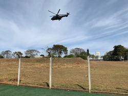 HFAB. A helicopter of aeronautics, at the height of the trees, the image of nature with very dry lawn, soot of grass in the air, the blue sky at dawn with clear clouds