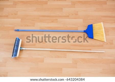 Hgh angle view of long handle brooms on hardwood floor