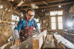Hhot of old master carpenter working in his woodwork or workshop. DETAILS
