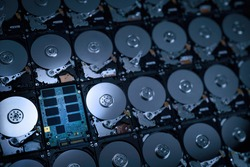 hi resolution photograph wallpaper of numbers of hard disk drives show inside metal disk and parts in pattern with focusing on the one of circuit of solid stage drive in cool blue tone light and shade