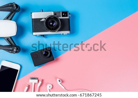 Hi tech travel gadget and accessories on blue and pink copy space