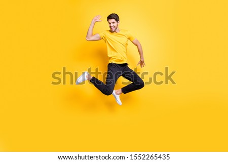 Hi there guys! Full body photo of handsome guy jumping high waving arm see old friends on streets wear casual t-shirt black trousers isolated yellow color background