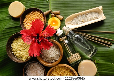 hibiscus,salt ,in wooden bowl ,bottle oil, soap.candleand banana leaf texture