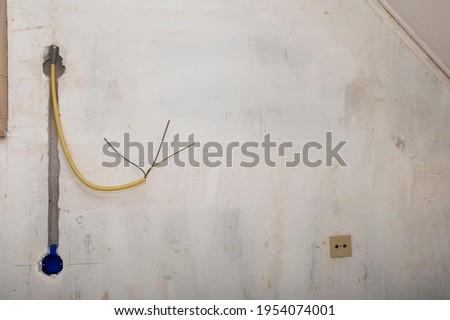 Hidden installation of electrical wires for sockets to a concrete wall.  Repair in an old apartment and transfer of sockets. Photo stock ©