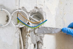 hidden installation of electrical wires for sockets to a concrete wall. The master is plastering the strobes with the wire before the molar works. repair in an old apartment and transfer of sockets.