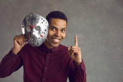 Hidden personality: Happy kind handsome young black man isolated on grey studio background takes creepy ugly maniac mask off his face, looks at camera, points up and smiles to show he can be different