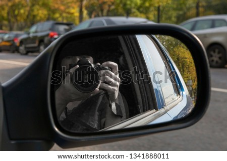 Hidden photographing from car window. Reflection in car mirror of hands with camera. Paparazzi concept