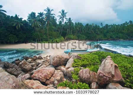Stock Photo Hidden secret lonely paradise beach with boat on the shore at Mirissa, Sri Lanka