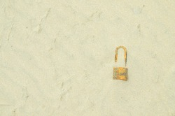 Hidden treasure on sand. The key is locked on the concrete floor. A  rusted padlock lies against a background of desert sand.
