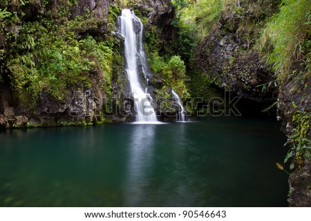 hidden waterfall in Maui wood with pristine water in a small pond