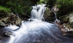 Hidden waterfall in the middle of forest. Pure natural scene. Clean nature. Flowing falling water, stones and grass surrounding the river.