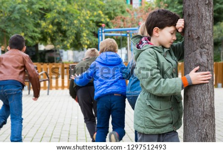 Hide and seek. Preteen boy closing his eyes and counting while other children hiding during games outdoors