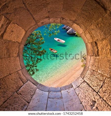 Hiden beach in Brela with boats on emerald sea aerial view through stone window, Makarska riviera of Dalmatia, Croatia Сток-фото ©