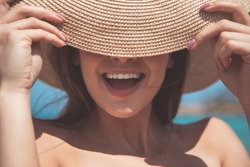 Hiding from the sun. Close up of excited girl is covering her eyes by hat and laughing. She is relaxing at the sea