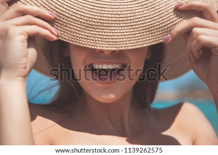Hiding from the sun. Close up of excited girl is covering her eyes by hat and laughing. She is relaxing at the sea  #1139262575