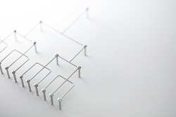 Hierarchy, command chain, company / organization structure or layer concept image. Top down structure made from chrome wires and chrome nails on white. Shallow depth of field.
