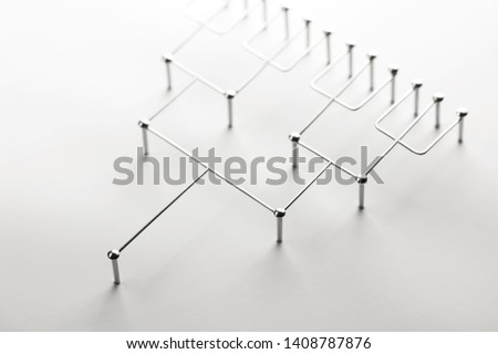 Hierarchy, command chain, company / organization structure or layer concept image. Tournament bracket structure made from chrome wires and nails on white. Shallow depth of field.