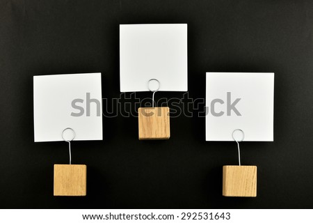 Hierarchy - Three white paper notes with wooden holders isolated at black paper background for presentation