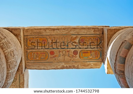 Hieroglypic carving and paintings on ceiling wall at the ancient egyptian Karnak temple in Luxor with columns