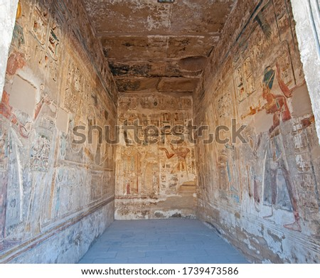 Hieroglypic carvings and paintings on interior room wall at the ancient egyptian temple of Medinat Habu in Luxor