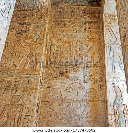 Hieroglypic carvings and paintings on wall at the ancient egyptian temple of Medinat Habu in Luxor
