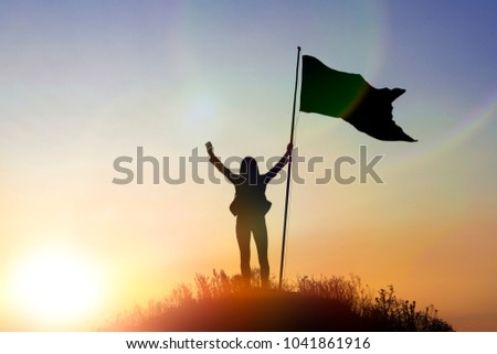 High achievement, silhouettes of the girl, flag of victory on the top of the mountain, hands up. A man on top of a mountain. Conceptual design. Against sky with clouds at sunset. business concept