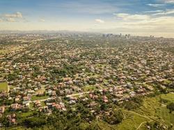 High Aerial of Katarungan Village, Ayala Alabang Village, and Metro Manila cityscape. Sheer size of built up area of Mega Manila.