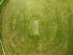 High aerial photo of cricket pitch field, green grassed with oval pattern, sunny summer day