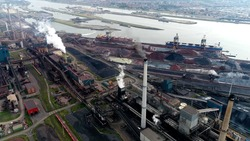 High altitude aerial photo of steelmaking factory heavy industry exhaust fumes everywhere also showing the steel commodities at the coast and in background large sluice