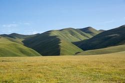 High altitude mountains with grassland landscape