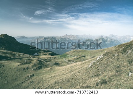 High altitude pasture, rocky mountain peaks and jagged ridge, with scenic sky, the Italian Alps. Expansive view in backlight. Toned desaturated image.